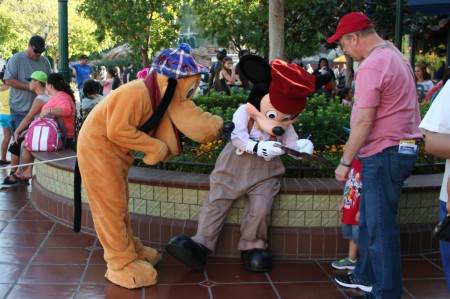 Mickey signs an autograph while faithful Pluto looks on