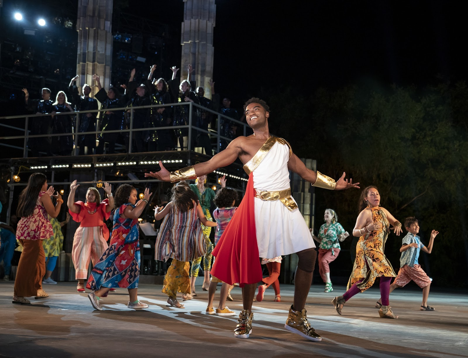 Jelani Alladin (foreground) and the company of The Public Theater's free Public Works musical adaptation of Hercules, with music by Alan Menken, lyrics by David Zippel, book by Kristoffer Diaz, choreography by Chase Brock, and directed by Lear deBessonet, running at the Delacorte Theater. Photo credit: Joan Marcus.